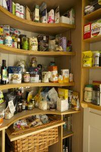 Full height bespoke larder cupboard with oak shelving and spice racks
